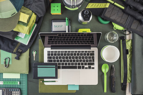 Overhead view of laptop, external hard drive and hiking equipment, green - CUF19008