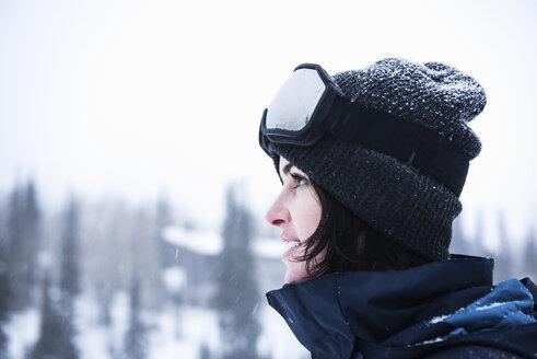 Portrait of young woman wearing ski goggles gazing at snow, Brighton Ski Resort outside of Salt Lake City, Utah, USA - CUF19104