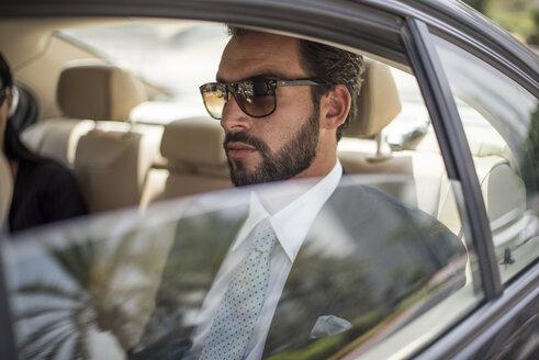 Young businessman wearing sunglasses in car backseat, Dubai, United Arab Emirates - CUF19113