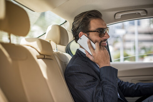 Young businessman in car backseat wearing sunglasses and talking on smartphone, Dubai, United Arab Emirates - CUF19116