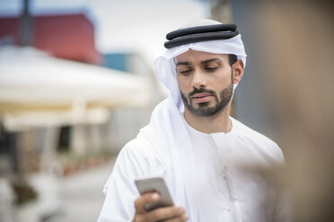 Man wearing traditional middle eastern clothing reading smartphone text, Dubai, United Arab Emirates - CUF19122
