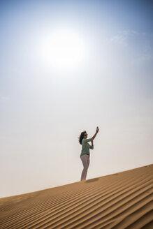 Woman tourist taking smartphone selfie on desert dune, Dubai, United Arab Emirates - CUF19137
