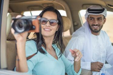 Female tourist in off road vehicle in desert taking photographs, Dubai, United Arab Emirates - CUF19143