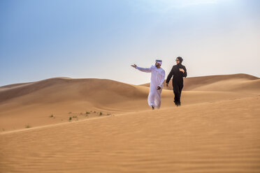 Couple wearing traditional middle eastern clothes pointing from desert dune, Dubai, United Arab Emirates - CUF19146