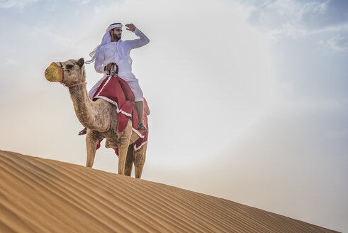 Man wearing traditional middle eastern clothes riding camel in desert, Dubai, United Arab Emirates - CUF19149