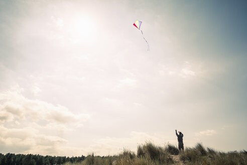 Silhouetted man flying a kite on Norfolk coast, UK - CUF19203