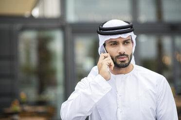 Man wearing dishdasha walking along street talking on smartphone, Dubai, United Arab Emirates - CUF19209