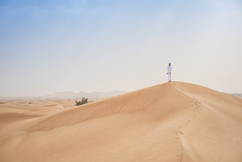 Young middle eastern man wearing traditional clothes looking out from desert dune, Dubai, United Arab Emirates - CUF19212