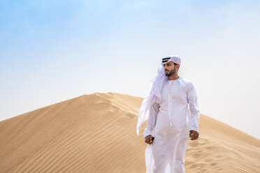 Middle eastern man wearing traditional clothes on desert dune, Dubai, United Arab Emirates - CUF19215
