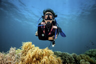 Young woman looking at hard and soft corals whilst scuba diving, Moalboal, Cebu, Philippines - CUF19281