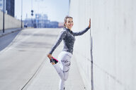 Female runner stretching legs during urban workout - BSZF00440