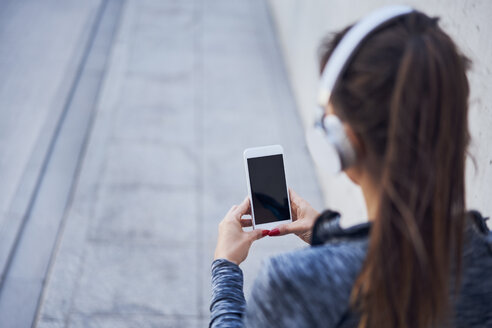 Woman with headphones using smartphone - BSZF00452