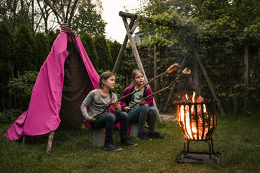 Two girls wearing feather headdress, with twist bread on camp fire - MOEF01211