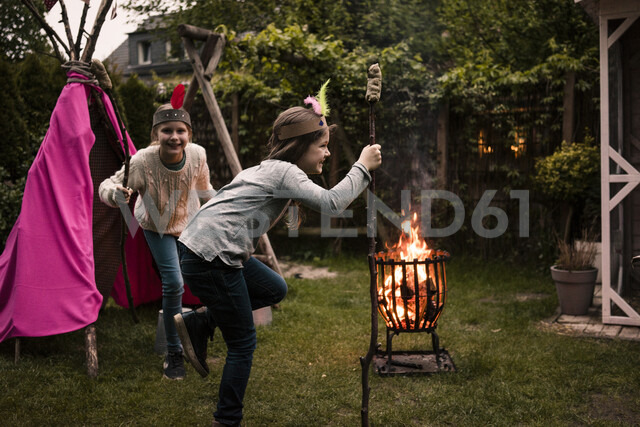 Two girls wearing feather headdress, dancing with twist bread around the camp fire - MOEF01214