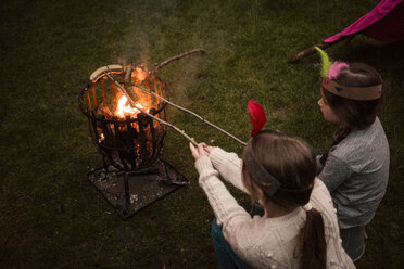 Two girls wearing feather headdress, grilling sausage over camp fire - MOEF01217