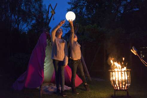Two girls standing in front of tipi, holding lamp as moon - MOEF01223