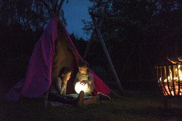 Two girls sitting in tipi, holding lamp as moon - MOEF01226