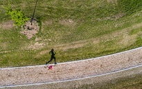 Aerial view of female jogger on woodchip trail - STSF01591
