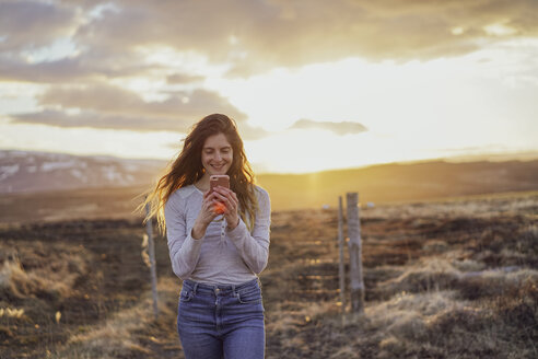 Iceland, young woman using smartphone at sunset - AFVF00556