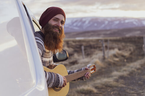 Iceland, young man sitting in van and playing guitar - AFVF00562