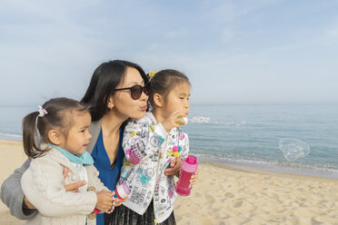 Mother with two daughters blowing soap bubbles on the beach - AFVF00565