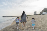 Mother with two daughters running on the beach - AFVF00568