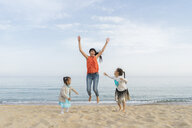 Happy mother with two daughters playing on the beach - AFVF00571