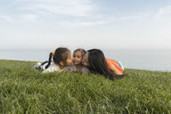Mother with two daughters kissing at the coast - AFVF00574