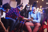 Friends using mobile phone at Halloween party - ABIF00466