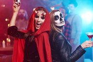 Women in creepy costumes dancing at Halloween party - ABIF00508