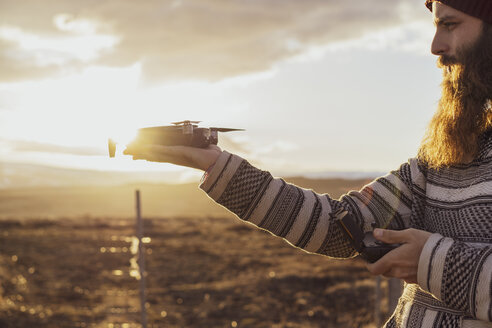 Iceland, bearded man holding a drone at sunset - AFVF00577
