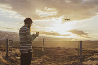 Iceland, bearded man piloting a drone at sunset - AFVF00580