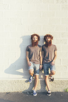 Portrait of identical adult male twins with red hair and beards against white wall - CUF19806