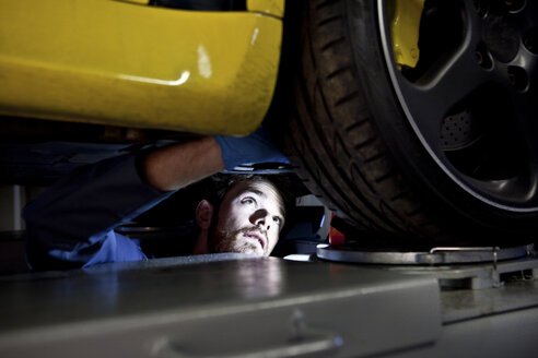 Male mechanic underneath car, looking for problem - CUF20046
