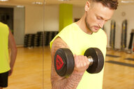 Tattooed man at gym lifting dumbbells - CUF20049