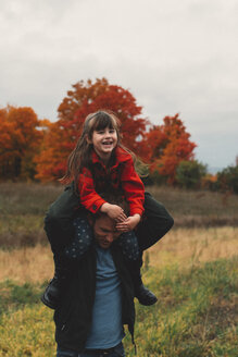 Mid adult man giving daughter a shoulder carry in field - ISF07433