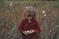 Girl holding wildflower pods in field of long grass - ISF07436