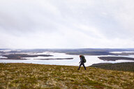 Hiker by lake, Keimiotunturi, Lapland, Finland - CUF20084