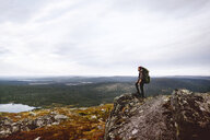 Hiker enjoying view on cliff top, Keimiotunturi, Lapland, Finland - CUF20090