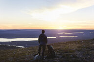 Hiker enjoying sunset at lake, Keimiotunturi, Lapland, Finland - CUF20093