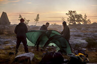Hikers setting up tent at sunset, Sarkitunturi, Lapland, Finland - CUF20096