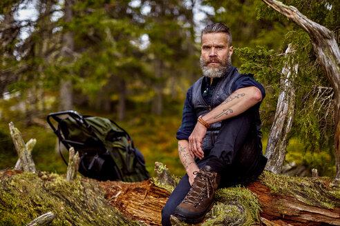Hiker resting on fallen tree, Sarkitunturi, Lapland, Finland - CUF20108