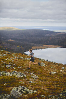 Man trail running on rocky cliff top, Keimiotunturi, Lapland, Finland - CUF20114