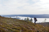 Hiker crossing field by lake, Keimiotunturi, Lapland, Finland - CUF20132