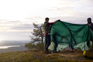 Hikers setting up tent on hilltop, Keimiotunturi, Lapland, Finland - CUF20138