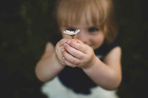 Girl holding up daisy flower smiling - CUF20150