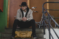 Bearded man wearing black hat, sitting on steps, travel bag - AFVF00590