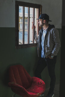 Bearded man wearing black hat, looking out of window - AFVF00593