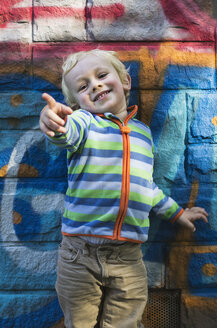 Portrait of smiling little boy standing in front of colourful wall pointing on something - MUF01529