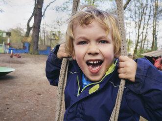 Portrait of screaming little boy on playground - MUF01532